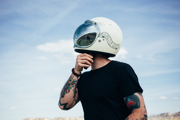 Shot from below of brutal man with arm tattoos and hipster tshirt, prepares for motorcycle ride, by wearing vintage retro helmet with huge reflective visor