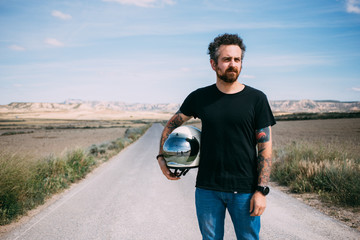 Brutal man with beard and arm tattoos poses with vintage retro helmet in blank mockup black tshirt in middle of american highway