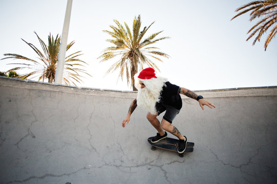 Funny cute man dressed like santa claus finally has summer vacation holidays, rides skateboard inside pool with amazing sun light leaks and palm trees