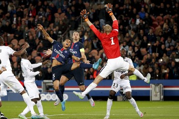 Paris St Germain's Zlatan Ibrahimovic and Gregory Van Der Wiel jump in front Guingamp's goalkeeper Jonas Lossl during their French Ligue 1 soccer match at Parc des Princes stadium in Paris