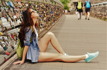 Wedding Locks. A girl with beautiful legs sits on a bridge