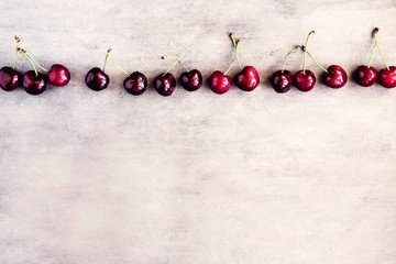 Raw of fresh cherries on concrete background. Copyspace for text. Summer fruit detoxing concept