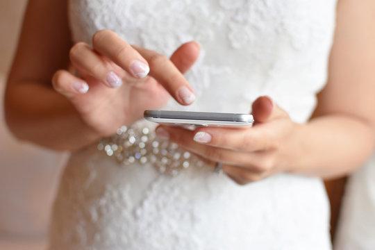 Bride in wedding dress holding smartphone in hands