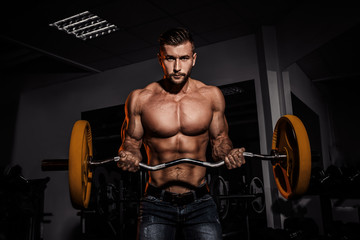 man in gym. Muscular bodybuilder guy doing exercises with barbell. Strong person. Sports background. Young athlete ready for weight lifting training