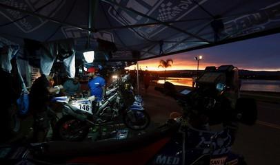 Mechanics work on the Yamaha motorcycle of Julian at sunset in the Dakar Rally 2016 bivouac in Carlos Paz