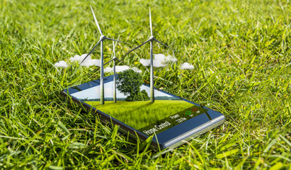 Modern mobile phone and wind turbines in nature as a smartphone-app to control power and lights at home