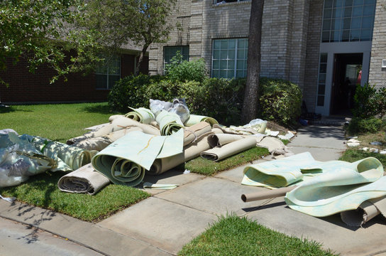 Carpet rolls in front yard of installation with piles of debris