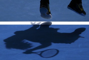 Williams of the U.S. casts a shadow as she serves during her quarter-final match against Russia's Sharapova at the Australian Open tennis tournament at Melbourne Park