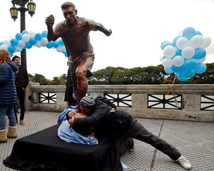 A man grabs and kisses the statue of Argentina's soccer player Messi after it was unveiled in Buenos Aires