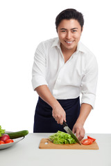 Attractive mature chef wearing a white shirt and black apron, standing chopping vegetables for a fresh salad. White background.