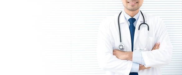 Smiling doctor standing and crossing his arms in white blind background