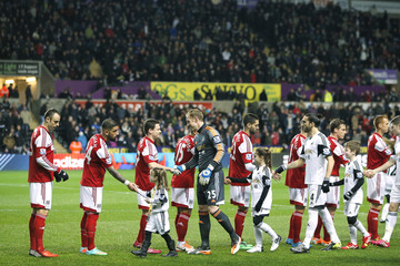 Fulham and Swansea City players shake ands before the start