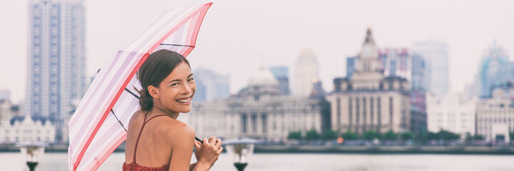 Chinese umbrella woman in rain background banner. Urban landscape panorama of Shanghai city Bund, Pudong Huangpu district, rainy summer day. Tourist traveling in Shanghai, China, Asia travel.