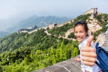 Wall Mural - Happy tourist girl at Great Wall of china doing thumbs up hand sign having fun at famous Badaling ruins during travel holidays at Chinese destination. Asia vacation.