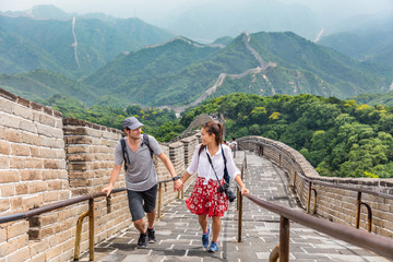 Wall Mural - Happy couple tourists holding hands walking up the Great wall of china, top worldwide tourist destination. Young multiracial people travelers during Asia vacation.