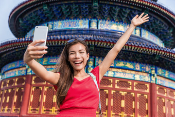 Happy Asian tourist taking fun selfie at famous tourist attraction in Beijing, china. Asia summer travel. Young woman taking mobile picture with phone at temple of heaven.