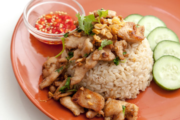 Fried pork with garlic over rice served with vegetable and chili sauce