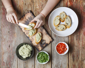 Preparation of bruschetta. Closeup view from above, female hands prepare traditional Italian bruschettes.