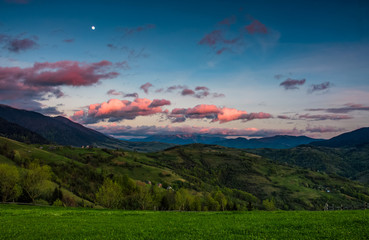 countryside landscape in mountains at dusk and moonrise