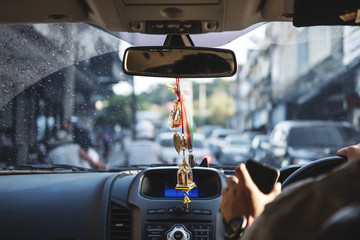 Modern car interior with hanging amulets charm on rear view mirror, driving on the road