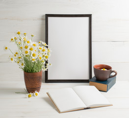 Daisy bouquet with open  notebook and motivational frame on background of  wooden planks in scandinavian style
