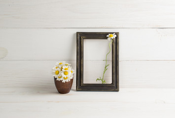 Daisy bouquet in clay vase and photo frame