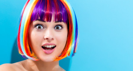 Wall Mural - Beautiful woman in a colorful wig on a blue background