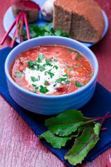 Ukrainian traditional borsch. Russian vegetarian red soup  in blue bowl on red wooden background.  Borscht, borshch with beet. Close up.