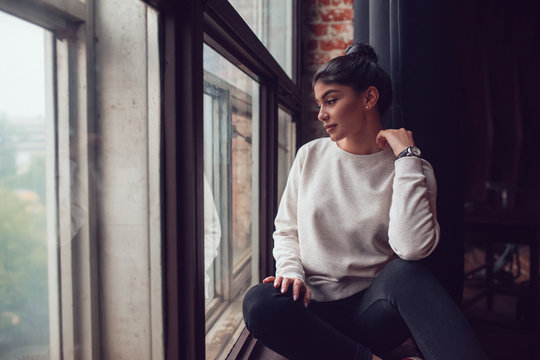 Attractive woman in gray sweatshirt sits on window sill and looks out the window. Mock-up.