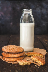 Bottle with milk and a stack of cookies on a dark background, retro style, vintage
