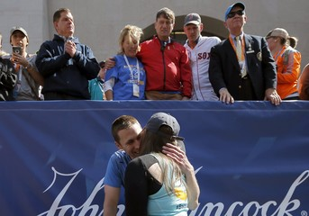Boston Marathon bombing survivors Patrick and Jessica Downes hug after the 120th running of the Boston Marathon in Boston, Massachusetts