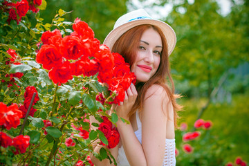 Beautiful and nice redhead woman in white hat in vacation spending a good time. Girl in white and pink light blue tones at clothes