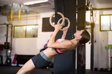 Young attractive woman exercise on rings