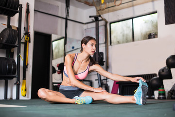 Young woman is stretching in gym