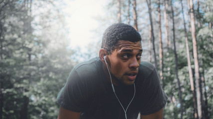 African American man preparing for a jog on a forest road. Young athletic male exercising outdoors