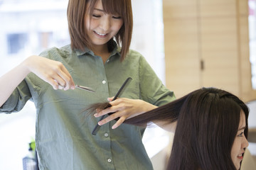 Hairdressers are cutting women's damaged hair