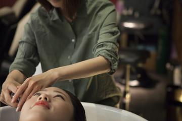 Hairdresser is rinsing customer's hair