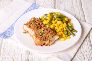 Baked codfish in breadcrumbs and vegetables on a white plate