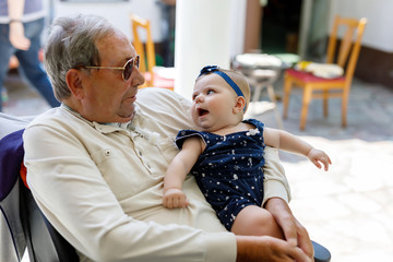 Cute little baby girl with grandfather on summer day in garden