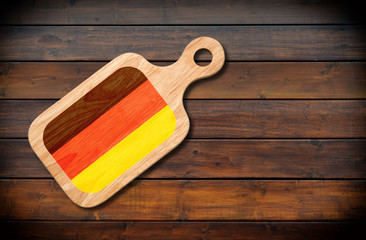 Concept of German cuisine. Cutting board with a German flag on a wooden background