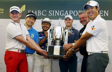 Golfers pose the trophy during a news conference ahead of the SMBC Singapore Open golf tournament at Sentosa's Serapong golf course