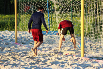 Young men play football in the summer on the sand platform. A goal is scored.