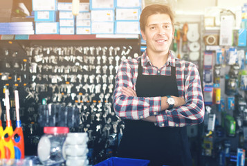 worker in hardware store trading goods for water tap in uniform
