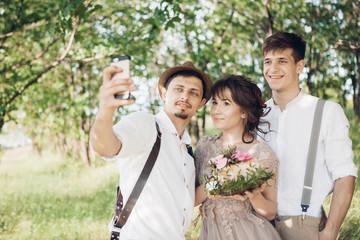 Wedding photographer, bride and groom make selfie in nature