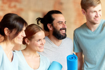 group of people with mats at yoga studio or gym