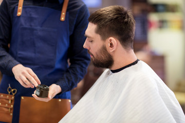 barber showing hair styling wax to male customer