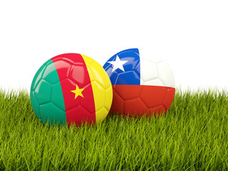 Two footballs with flags of Cameroon and Chile on green grass