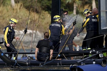 Skipper Nathan Outteridge sprays the crew of Artemis Racing aboard their AC45F racing sailboat after winning the America's Cup World Series sailing competition on the Great Sound in Hamilton