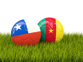 Two footballs with flags of Chile and Cameroon on green grass
