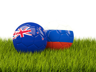 Two footballs with flags of New Zealand and Russia on green grass